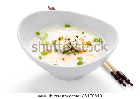 Rice porridge, or jook with boiled quail eggs in white bowl with chopsticks on white background.