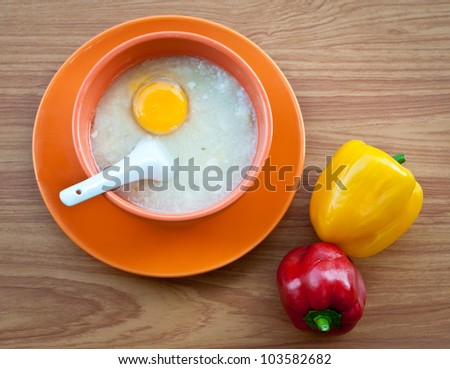 Rice porridge with egg in orange bowl on wood table with paprika .
