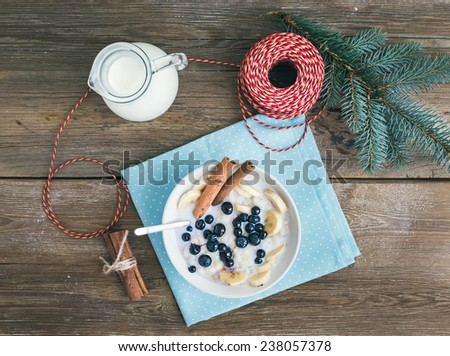Rice porridge with milk, cinnamon, banana and blueberry with Christmas (New Year) decorations on a rustic wood background. Top view #238057378