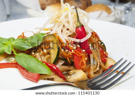 Rice spaghetti with vegetables on a white plate in a restaurant