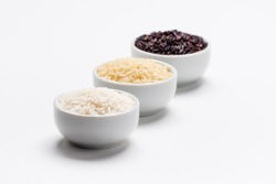 Rice the staple food of the world. 3 varieties of rice, white jasmin, basmati and black rice in white bowls on white background with copy space. Rice is the most consumed staple food ingredient.