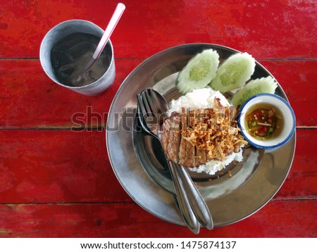 rice topping with fried garlic pork, serve with fresh cucamber and chili fish sauce on aluminum dish or zinc dish on red wooden table