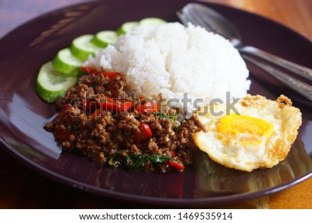 Rice with basil, fried egg, in a dark color dish, national dish of Thailand