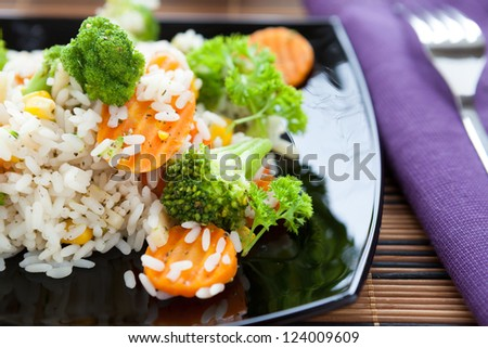 rice with carrots and broccoli on a black plate, close up