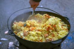 Rice with carrots, meat and spices when cooking pilaf in a cauldron