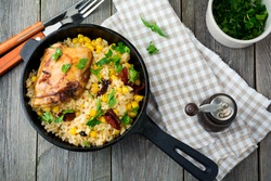 Rice with corn, soy sauce and fried chicken thigh on a cast-iron frying pan. Top view. Selective focus.