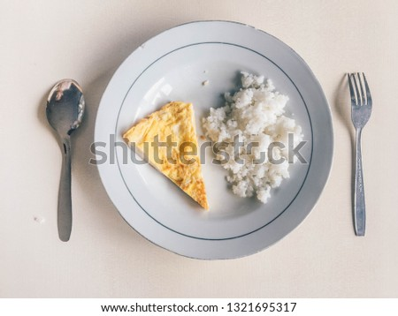rice with fried egg with fork and spoon on white plate isolated on white background. Poor man dish or simple dish for breakfast.
