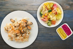 rice with mussels and carrots on a white  plate. rice with mussels and carrots on a blue wooden  background. rice with vegetable salad and sauce top view.asian food  flat lay