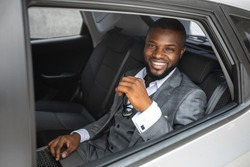 Rich african american young businessman smiling through open car window. Cheerful handsome black man in stylish suit going to business trip by car, sitting on back seat and looking through window