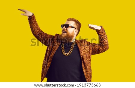 Rich bearded man in leopard print outfit and cool glasses vibing to music. Happy redhead showman, funny party guy, showbiz entertainer, glamour show presenter, night club goer dancing and having fun