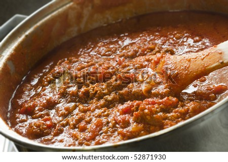 Rich Bolognese sauce cooking in a saucepan, with wooden spoon, ready for your pasta dish.