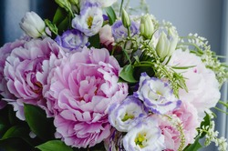 Rich bunch of pink peonies and lilac eustoma roses flowers, green leaf in glass vase. Fresh spring bouquet. Summer Background