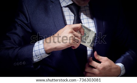 rich business man holding dollars cash on black background #736303081