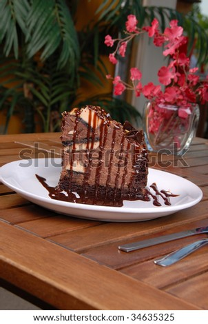 Rich Chocolate filled cake with creamy chocolate all over it. Table setting flower in background with focus on dessert. Slight angled portrait photo.