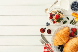 Rich continental breakfast background. French crusty croissants, muesli, lots of sweet berries and hot coffee for tasty morning meals. Delicious start of the day. Top view, copy space on white wood