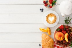Rich continental breakfast. French crusty croissants, muesli, lots of sweet fruits and berries, hot coffee for morning meals. Delicious start of the day. Top view with copy space on white wooden table