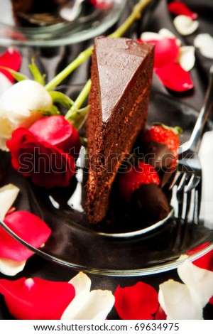 Rich dark chocolate cake with mousse filling accompanied by chocolate covered strawberries and champagne