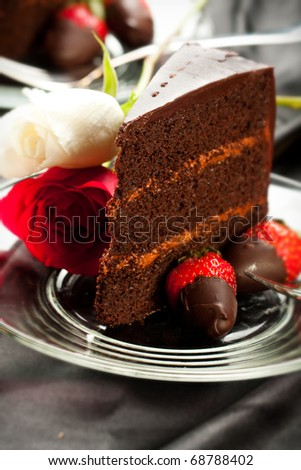 Rich dark chocolate cake with mousse filling accompanied by chocolate covered strawberries and roses