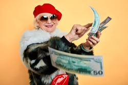 rich elegant woman in fur coat and red cap throwing money, spending money on useless thing, isolated yellow background. studio shot,