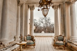 Rich interior of studio with gold decorations on the walls. Large white columns. Balcony or loggia, interior in the style of Borocco.