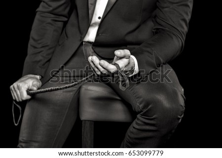 Rich man sitting on bar stool and holding whip, black and white, bdsm #653099779