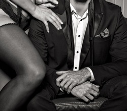 Rich man with lover in underwear posing on sofa, closeup, black and white
