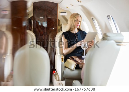 Rich mid adult woman using tablet computer in private jet ストックフォト ©
