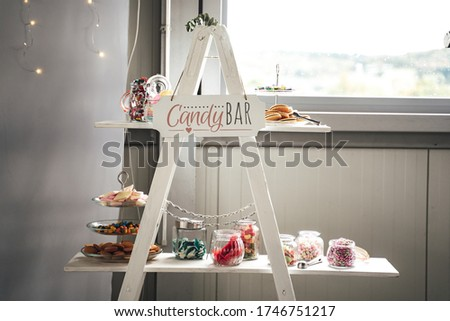 Rich offer of colorful candies in glass jars and on plates laying on white stand. Lettering Candy bar. Wedding or party concept.