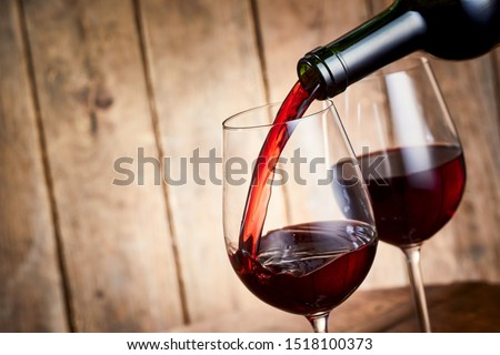 Rich red cabernet wine pouring into a a stylish wineglass from a bottle in a close up tilted angle view over rustic wood Foto stock ©
