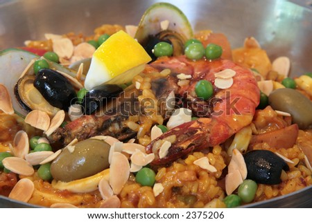 Rich seafood paella with baked almond slices and whole olives - stock photo