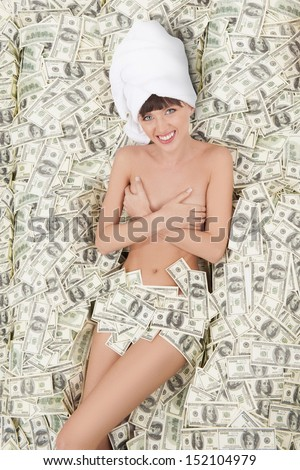 Rich woman. Top view of naked smiling woman lying on the US paper currency