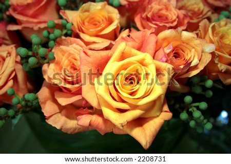Rich yellow-orange roses arranged with green berries at a wedding reception