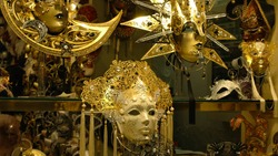 Richly decorated display case. Golden carnival masks, faces covered with mother-of-pearl and pallets.