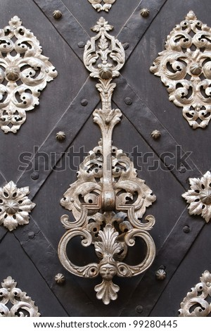 richly decorated doors with wrought iron, and knocker