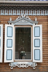 Richly decorated ornamental carved window and frame on vintage wooden rural house in Chita city, Russia. Russian traditional national folk style in wooden architecture. Chita landmark, Chita monument
