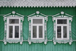 Richly decorated ornamental carved windows, frames on vintage wooden rural house in Suzdal town, Vladimir region, Russia. Russian traditional national folk style in wooden architecture. Countryside