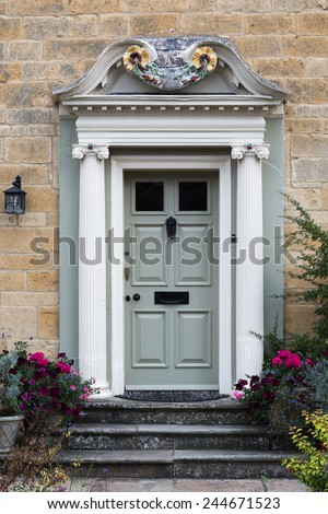 richly decorated wooden front door with pillars placed in a limestone facade