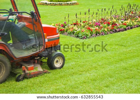 Ride on lawn mower cutting grass - Image with copy space #632855543