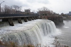Rideau Falls in Ottawa in early winter. Waterfall cascading in Ottawa, Ontario, Canada. Rushing white water on a cold, overcast day in the national capital of Canada.
