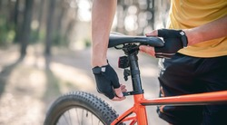 Rider adjusting seat height on bicycle standing in sunny forest