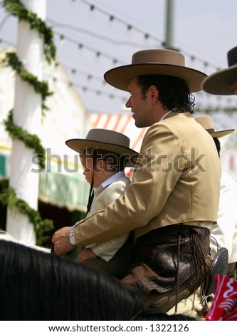 Rider Andalusian with a boy, mounting on a horse in the fair of April Seville