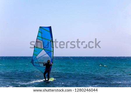 Rider in Wetsuit and Helmet Balancing on a Surfboard with Sail Mast and Bar. Clear Sky and Blue Wave. Surfer Trying out the Outdoor Water Sport Adventure. #1280246044