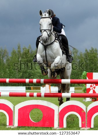 Rider jumping with white horse over obstacle