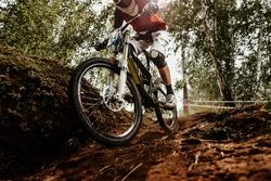 rider of bike downhill mountain biking trail in sunlight
