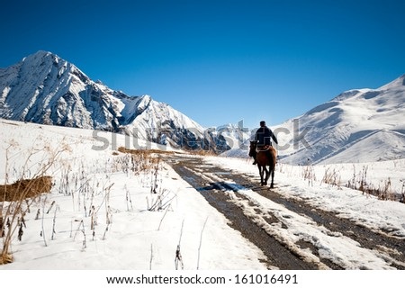 rider on a horse into the Caucasus Mountains of Georgia