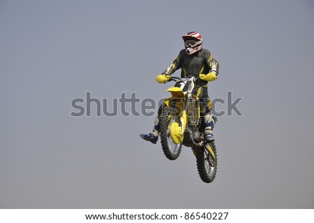 Rider on a motorcycle flying through the air against the sky