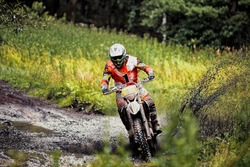 rider on a motorcycle rides a puddle of mud, splashing around, competitions in extreme Enduro