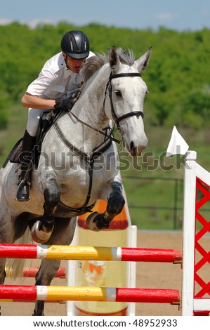 Rider on gray horse in jumping show