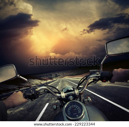 Rider on the motorcycle moving towards dark storm clouds on the asphalt road