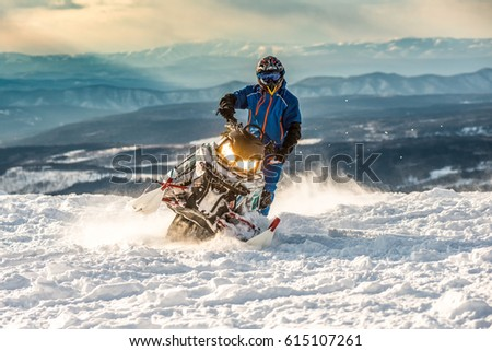 Rider on the snowmobile in the mountains ski resort in Amut Russia. - Shutterstock ID 615107261